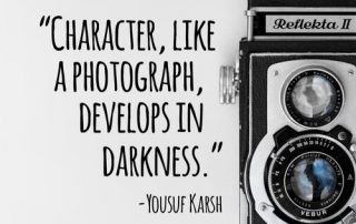 "Old camera with quote next to it ""Character, ike a photograph, develops in the darkness."" - Yousuf Karsh"