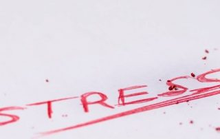 "The word ""stress"" written on a piece of paper in red ink."