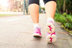 Image shows tennis shoe clad feet walking along rain cleansed suburban sidewalk - illustrating that walking and moving helps reduce pain.