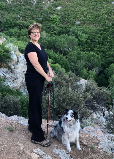 Becky Curtis with dog on mountain trail